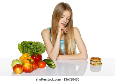 Woman making decision between healthy food and fast food, over white background