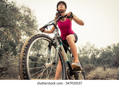 Woman making downhill with mountain bike. Concept about people and sport