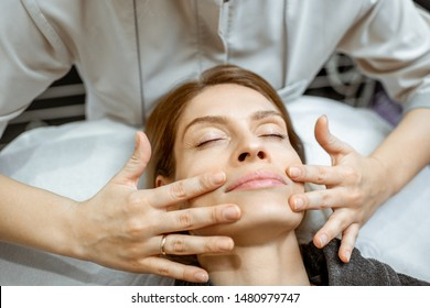 Woman making facial massage at the beauty salon. Concept of a lymph drainage therapy