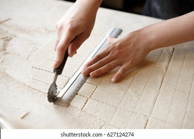 Woman making farfalle pasta at a restaurant. Cutting the dough with a cutter and a ruler