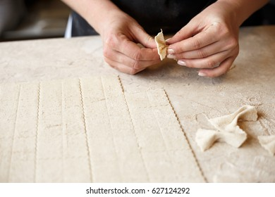 Woman making farfalle pasta at a restaurant. Lots of copy space for text