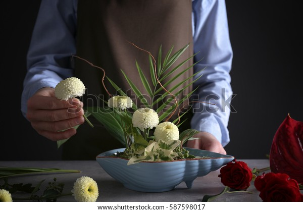 Woman making floral composition at wooden table