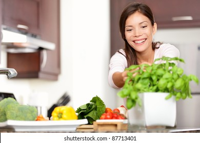 Woman making food in kitchen reaching for basil plant. Healthy eating concept with beautiful happy smiling multiracial Caucasian / Asian woman at home.