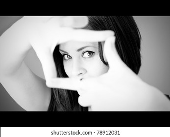 A woman making a frame with her fingers in widescreen movie format in black and white.