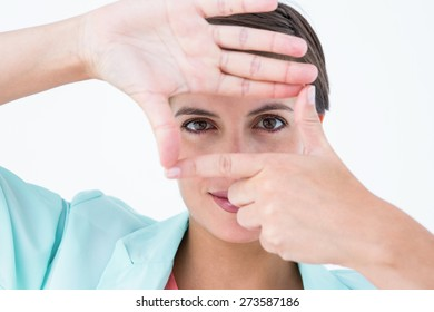 Woman making frame with her hands over white background