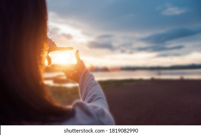 The woman making frame round the sun with her hands in sunrise,Future planning idea concept.