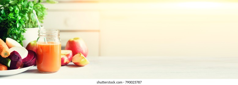 Woman making fresh drink. Juicer and carrot juice. Fruits in background. Clean eating, detox concept. Banner