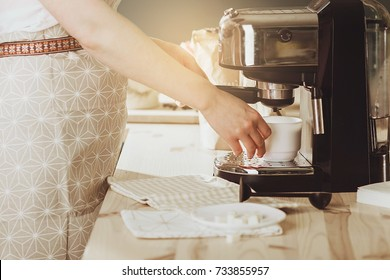 Woman making fresh espresso in coffee maker. coffee machine makes coffee. Barista Coffee Maker Machine Grinder Portafilter Concept