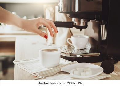 Woman making fresh espresso in coffee maker. coffee machine makes coffee. Barista Coffee Maker Machine Grinder Portafilter Concept