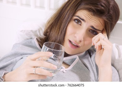 Woman making funny expression sick in bed