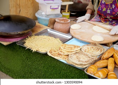 A woman making  Gozleme. Gozleme is a traditional Azerbaijan  dish featuring flat bread stuffed with a range of delicious fillings. Baked on sheet iron