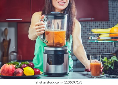 Woman making green smoothie on the kitchen. Focus on the blender.