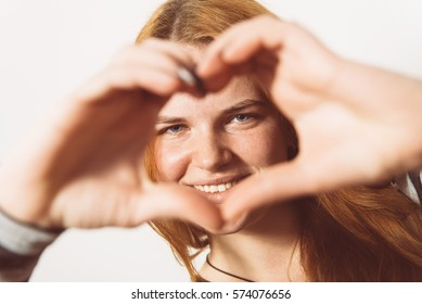 woman making a hand heart frame