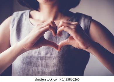 Woman making hands in heart shape, heart health insurance,social responsibility, gratitude,donation, happy charity volunteer, world heart day,  appreciation concept, world mental health day