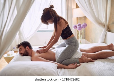 Woman making happy man erotic massage at home.