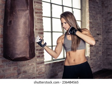 woman making hard boxe training  at the heavy bag. concept about sport and people