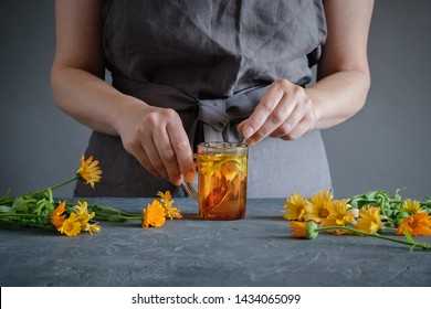 Woman making healthy tea with calendula or marigold flowers.