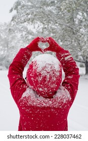 Woman making heart symbol with snowy red gloves