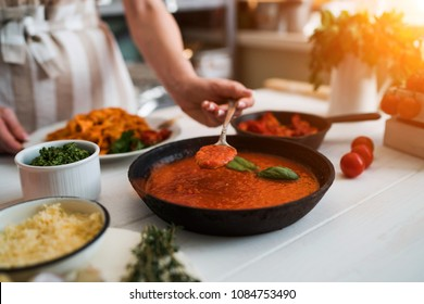 Woman making homemade pasta with tomato sous and cheese over old wooden table. Tomato, olive oil, spices, herbs, cheese, tomato sauce on a weathered wooden table in the summer sun's rays. Organic food