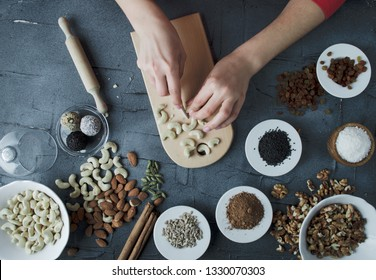 woman is making homemade sweets from nuts and dried fruits without sugar. top view with hands on black concrete background