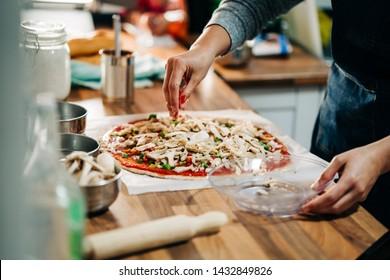 woman making homemade vegetarian pizza