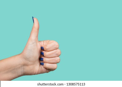 Woman making like gesture putting thumb up. Female hand with modern blue gel polish manicure isolated on green background. Horizontal color photography.