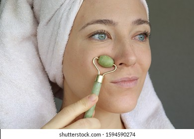 Woman making massage with green jade roller. Beauty tools for face treatment. Funny face.