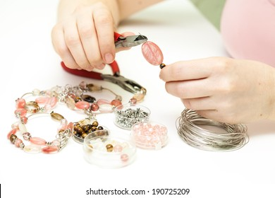 Woman making necklace from colorful gemstone beads