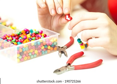 Woman making necklace from colorful wooden beads