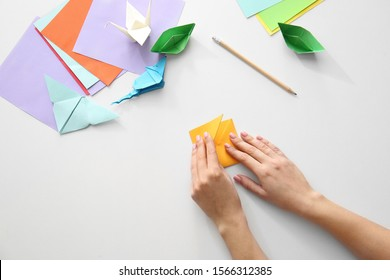 Woman making origami figures at table