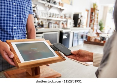 Woman making payment by smartphone at coffee shop, close up