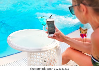 Woman making photo of exotic alcohol cocktail on white table on poolside