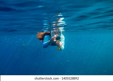 Woman making photo underwater. Girl snorkeling in full-face mask. Snorkel with fish under water surface. Snorkeling gear. Action camera. Active vacation by tropical seaside. Diving girl in open water