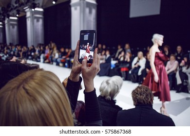 Woman making photo using her phone on a fashion show