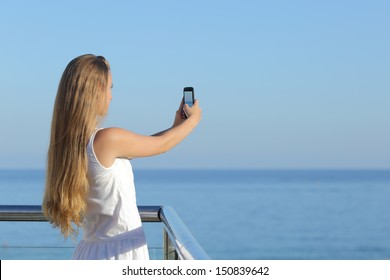 Woman making a photograph of the sea with a smart phone with the horizon over the sea in the background