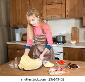 Woman making pizza at home kitchen.