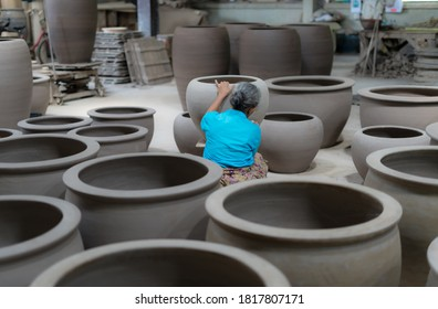 A woman making pottery in a factory