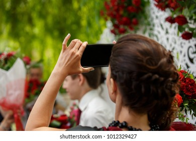 Woman making promo videoblog or photo session on wedding. Vlogger promotion selfie solution, journalist or blogger recording video with smartphone at wedding ceremony.