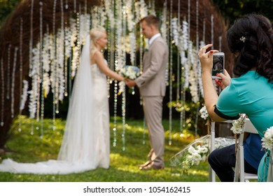 Woman making promo videoblog or photo session on wedding. Vlogger or journalist or blogger recording video with smartphone at wedding ceremony. Selective focus on woman with smart phone