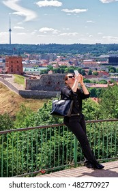 Woman making selfie with Gediminas Tower on the hill and the Lower Castle down the hill in Vilnius in Lithuania. The Tower is also called as Upper Castle. Lithuania is a Baltic country