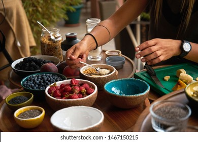 woman making smoothie bowl for breakfast. many useful fruits