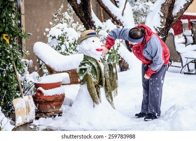 Woman is making a snowman in her front yard during snow storm