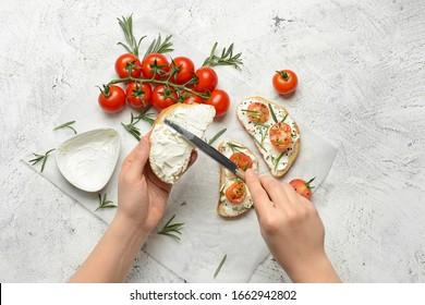 Woman making tasty sandwich with cream cheese on white background