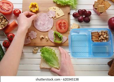 Woman making tasty sandwich on table