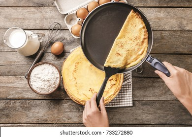Woman making thin pancakes on frying pan in kitchen