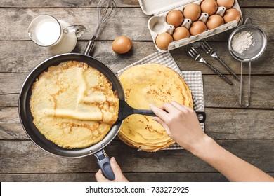 Woman making thin pancakes on frying pan in kitchen