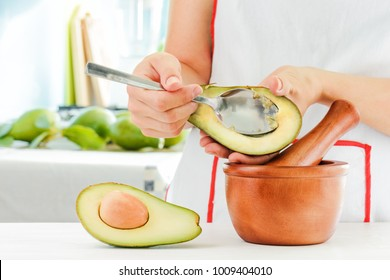 Woman making traditional Mexican sauce Guacamole from fresh avocados. Wooden mortar with pestle (molcajete) and half of ripe avocado on kitchen table. Healthy homemade vegetarian eco food.