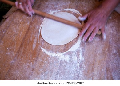 A woman making Turkish Gozleme. Gozleme is a traditional Turkish dish featuring flat bread stuffed with a range of delicious fillings. Baked on sheet iron.