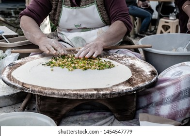 Woman making Turkish gozleme, a traditional flatbread rolled on a well worn wooden table and filled with green herbs and vegetables, cheese and spices before folding in half and cooking on a skillet.