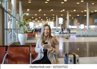 Woman making video call by modern tablet in airport waiting room and sitting near grey valise, showing thumbs up. Concept of communication, free hotspot and traveling abroad.